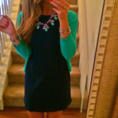 i love the black dress, green sweater and statement necklace...with heels or flats?