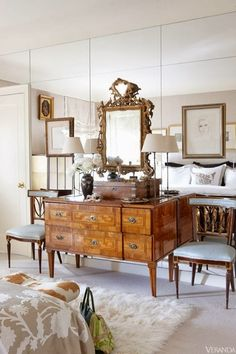 Light-filled vignette, antique gold-framed mirror on mirror wall, antique chest and chairs.  The floor-to-ceiling mirror makes this room modern.