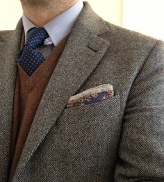 Dark grey tweed jacket, light blue shirt, navy tie with blue pin dots, brown sweater, light grey pants