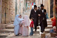 Jewish men Muslim children  Two Jewish men walk beside a small group of Muslim children in the Old City of Jerusalem