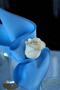 A blue linen napkin in a wine glass with a white rose makes an elegant accent to your table setting.