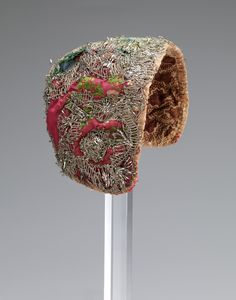 Child's cap, Norway, second half 18th century. Red silk brocade embroidered with flowers, silver metall lace decoration, block printed cotton lining.