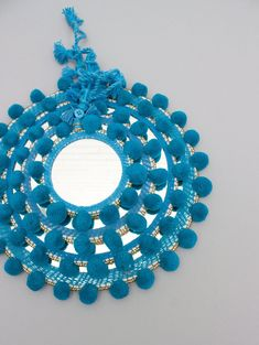 Our teal blue round pom pom mirror is handmade by artisans in India. The perfect fair trade boho home decor wall hanging accessory.