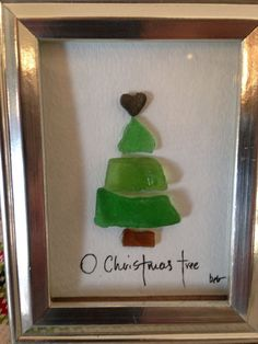 Sea glass Christmas tree, framed in a 2x3 shallow shadow box frame with hand lettering and a heart rock as the tree topper. Each tree is different as