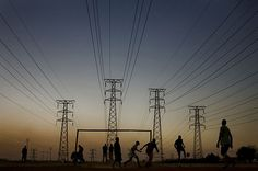 World Cup in South Africa  Photographed by Dominic Nahr / Reportage / Getty Images for TIME    A group of boys play soccer beneath power lines near the newly built Soccer City Stadium in Johannesburg.