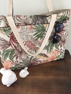 Maxi bolsa em tecido estampado, com grandes bolsos externos, forrada com tecido impermeável e com bolsos internos . Obs: objetos não incluídos.