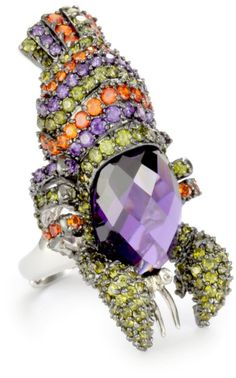 Huge Lobster ring that covered in cubic zirconia stones and featuring a large oval stone atop her head.
