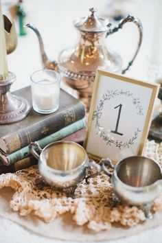 centerpieces with vintage books and silver accents- I have a silver tea pot