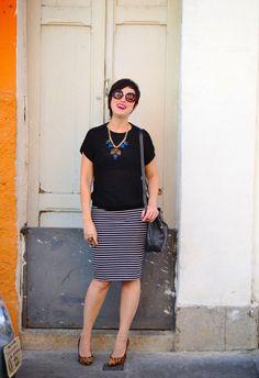 blusa tricô preta com colar dourado e peças de acrílico com brilhos, saia lápis listrada PB e scarpin onça com bolsa saco preta