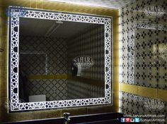 Grey bathroom mirror with sandblasted islamic design frame and backlight, surrounded by golden ceramic tiles,