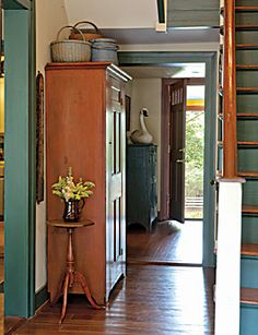 FARMHOUSE – INTERIOR – vintage early american farmhouse showcases raised panel walls, barn wood floor, exposed beamed ceiling, and a simple style for moulding and trim, like in this farmhouse hallway.