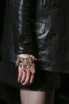 Grunge bracelets at Saint Laurent  For his second ready-to-wear collection as creative director at the house Saint Laurent, Hedi Slimane looked to 1990s grunge for accessories inspiration, with diamante and spiked stockings, biker boots and leather mini-dress paired with fine pearl necklaces and layered chains and charm bracelets.