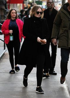 Ok, Adele is gracing New York with her presence. But WHAT in god's name is the woman in back of her doing? And wearing on her feet?