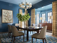 In the dining room, the family's midcentury sideboard is juxtaposed against vivid blue walls. Designer Andrew Howard blends the vibrant hue with patterns found in the custom rug and a classic paisley-print drapery fabric by Jasper by Michael S. Smith. The table is from Century, and the chairs are Mr. and Mrs. Howard for Sherrill Furniture. The chandelier is Baker Furniture.
