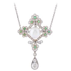 An Edwardian Natural Pearl Emerald Diamond Platinum Pendant. A Delicate Edwardian Platinum Natural Oriental Pearl, Emerald & Diamond Pendant, the lobed flowerhead lozenge cluster, set at the centre with a bouton pearl measuring 9.3mm, within a prunus blossom frame set with circular-cut diamonds, decorated with 10 small emeralds, supporting a pear-shaped drop, on a chain of trace linking. Circa 1910.