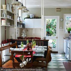 Die Weihnachtsdeko für den Esstisch besteht hier aus grünen Sektgläsern, einem roten Tischläufer und roten Pflanzen, die sich auf dem dunklem Holztisch im Vintage-Look…