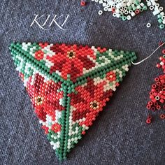 My new peyote triangle design with poinsettias in progress This pattern is available at: www.kikisbeads.com/poinsettiaspendant #beaded #peyote #pendant #pendants #beadedjewelry #beadedjewellery #unique #handmade #triangle #peyotestitch #peyotetriangle #handmadejewellery #handmadejewerly #handmadependant #christmas #peyotestitch #mydesign #flower #poinsettas #poinsettia #winterfashion #holiday #traditional #motifs #triangle #peyotependant #peyotestitch #christmasjewelry