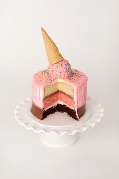 Neapolitan Cake | A trio of layers - chocolate, strawberry, and vanilla, iced with coordinating buttercream, glazed with a pink ganache drip and a charming melted ice cream cone topper with confetti sprinkles