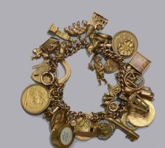 A charm bracelet. The yellow precious metal curb-link bracelet stamped '375', with 9ct gold padlock clasp, suspending a large collection of 9ct gold and yellow metal mounted charms, to include two sovereigns, two half sovereigns, dated 1892 and 1911, a 9ct gold 'Big Ben' charm and a 'St Pauls' charm