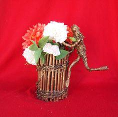 """""""blomstermanden"""" vase skabt af pinde, og genbrugsstof."""
