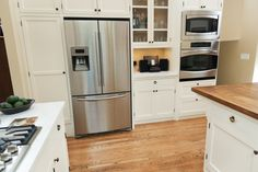 Light natural wood countertop reflects hardwood floor in this white kitchen punctuated by brushed aluminum appliances.