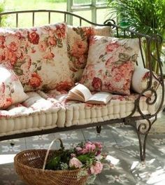 Rod iron bench with beige and floral cushions.  Garden, porch or outside seating