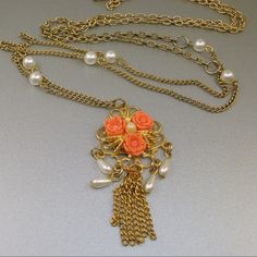 """Romantic Vintage Coral Flowers Necklace Long vintage necklace with a fringed pendant featuring molded plastic coral roses, faux pearls and a chain tassel. The pendant measures 2 1/2"""" long and comes on a 42"""" long gold tone metal chain. Part of the chain has faux pearls at intervals, and the other part has textured links...very different. This necklace is unsigned and in very good vintage condition...very feminine. Jewelry Necklaces"""