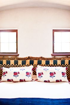 Textile with pattern hung as headboard for colorful, floral bed