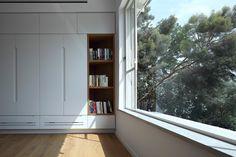 חלון ליער בן שמן מחדר השינה. בארון הבגדים שמול המיטה שולבו מדפי עץ פתוחים ( צילום :עוזי פורת )