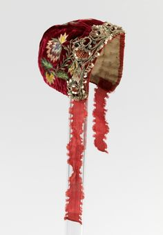 Infant's cap, Norway, 18th century. Red silk velvet with floral embroidery, red silk ribbon, linen lining.