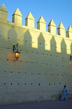 A woman walks under the ancient city walls of Fez, Morocco Moroccan Design, Moroccan Style, Morocco Travel, Africa Travel, Morocco Destinations, Ancient City, Fez Morocco, Desert Life, City Architecture