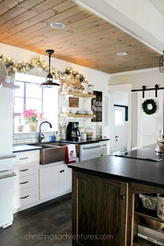Farmhouse Christmas Kitchen- so many things to love!  Barn door, subway tile, wood ceiling, open shelving, shiplap, copper sink and so much more!