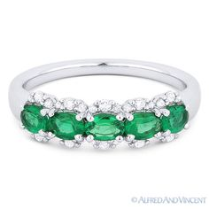 The featured ring is cast in 18k white gold and showcases 7 oval cut emerald gemstones set in 4-prong settings accentuated with round cut diamonds.
