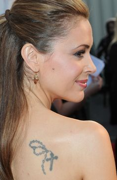 Alyssa Milano's tattoo: Alyssa Milano has a few tattoos herself, starting from two variations of the Buddhist symbol of wisdom AUM on her back neck and left wrist, continuing with a rosary lower on her back,