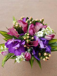 Bright purple vanda orchids with calla lillies n hypericum berries
