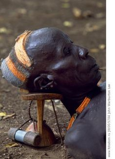 Ethiopia, Omo Valley, Duss. An elder of the Karo tribe rests with his head on his wooden head-rest which protects his elaborate clay hairdo....