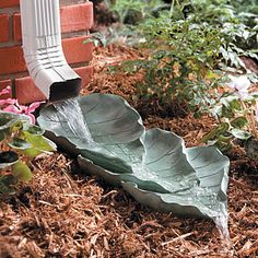 What a neat idea.  Make your cement leaf castings and stack them under the downspout.  Functional and so beautiful.