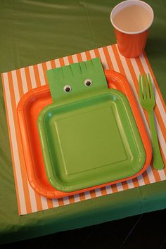 12×12 scrapbook paper as place mats paired with square plates and you have a great place setting. I used rectangular napkins and with some scissors cut slits in one end of the napkin to give it some monster hair. Adding googly eyes and now we have monster napkins!  I placed them between the plates like the monster was peeking out from behind the plate.