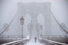 A man crosses Brooklyn Bridge