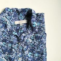 """LOFT Sheer Blouse Never worn. Petite small. Sheer, half button down, with collar. Blue floral pattern. Four white buttons, including one at neck. You will probably need a cami underneath, although because of the pattern it's hard to tell how sheer it is. One small left breast pocket. About 24.5"""" long from top of shoulder to hem. When laying flat: 19"""" from underarm to underarm; 20.5"""" wide near hem; 18.5"""" at waist (right under last/bottom button). 100% Polyester. LOFT Tops Button Down Shirts"""