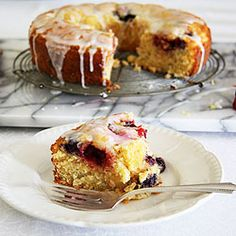 A fluffy, soft, lemon flavoured cake studded with strawberries and blueberries with a zesty lemon glaze