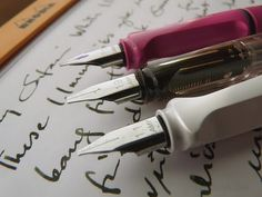 Lamy Pens. Pink & white safari. Dunno about the other one. Broad nibs.