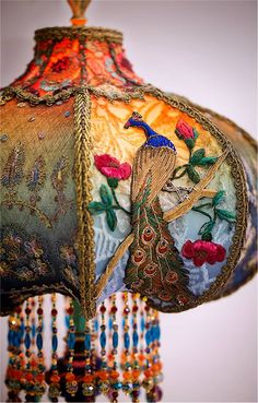 This gorgeous embroidered peacock (done in the Zardozi style) adorns a 1920's era table lamp.  The shade is silk and is hand painted and embellished with beading. The shade is ombré dyed in jewel tones of raspberry and amber into green and blue tones and has alternating panels of dyed burnout velvet and antique net lace with feather motifs.   Image courtesy of Christine Kilger's Nightshades lamp studio at http://www.nightshades.com/detail_lamps/1616.html