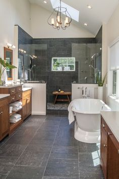 The Gardner/Fox team reconfigured the floor plan to accommodate a more spacious & luxurious master bath. The newly revamped master suite incorporates a large walk in shower with two shower heads, his & her vanities, a freestanding pedestal tub, and a makeup table with pendant lighting.