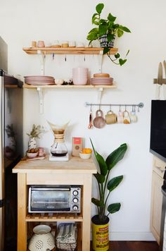 An IKEA cart and shelving in the kitchen hold Cai and Britt's ceramic dishes and mugs.