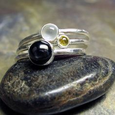 The white moonstone shimmers against a black night sky, with the promise of the golden sun in the morning.   Stacking rings from Lavender Cottage Jewelry