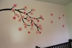 cut branch out of vinyl in several sections to make a huge branch on the wall. cut out cherry blossoms out of three different tones of pink cardstock and cut center out of brown cardstock. adhered to wall with glue dots. all done on silhouette cameo! love this machine!! this is on the nursery wall. -h.tracy
