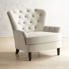 The charming Eliza offers timeless good looks with a classic silhouette draped in hand-upholstered, hand-tufted creamy velvet. A reversible, coil-spring seat cushion keeps things comfortable while turned wood legs up the elegance factor.