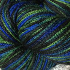 Abstract Fiber: SuperSock+ Diversity colorway. Rich shades of black, blue, and green. Diverse, multi-everything people bring color and richness to our lives. $5 of the purchase price will go to the ACLU so they can defend diversity. $33