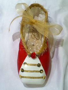 Here to protect our shoes is the Nutcracker Soldier! Painted in red and black with a white front. Jazzed up with dazzling gold ribbons and a red